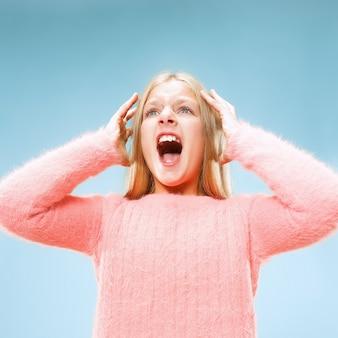 Изолированные на синий молодой случайный подросток девушка кричит в студии