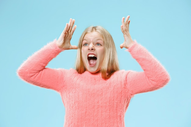 Изолированные на синий молодой случайный подросток девушка кричит на