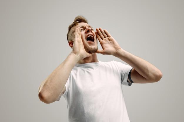Изолированные на серый молодой случайный человек кричит