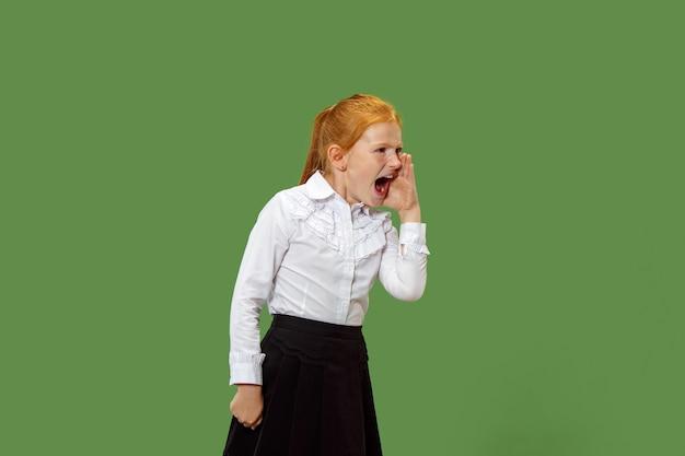 Изолированные на зеленый молодой случайный подросток девушка кричит в студии