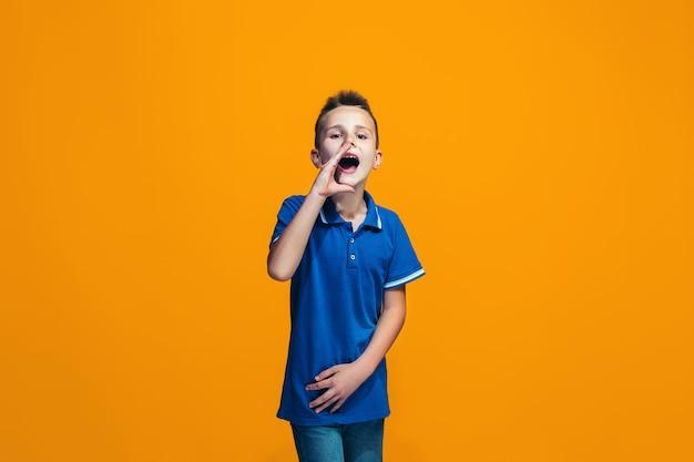 Изолированные на оранжевый молодой случайный подросток мальчик кричал