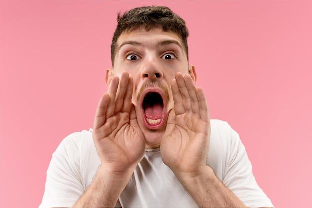 スタジオで叫んでいるピンクの若いカジュアルな男に孤立