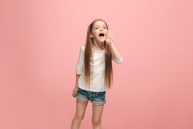 スタジオで叫んでいるピンクの若いカジュアルな十代の少女に孤立