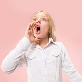 Изолированные на розовый молодой случайный подросток девушка кричит в студии
