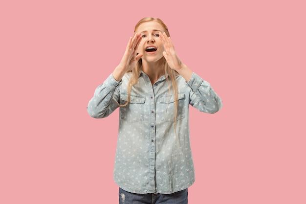 スタジオで叫んでいるピンクの若いカジュアルな女性に分離