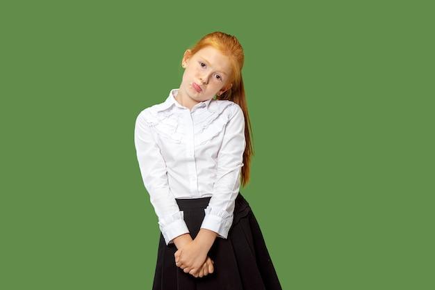 トレンディな緑のスタジオの背景に分離されました。若い感情的な驚き、欲求不満と当惑した十代の少女。