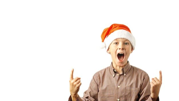 サンタクロースの帽子の開いた口を持つ白い背景の少年に分離されたインデックスの親指を示しています。バナー