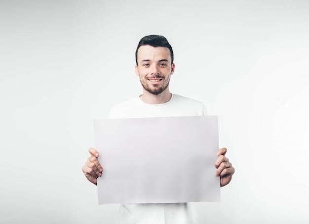 白い背景に分離された男はひげを生やしたポスターを保持します