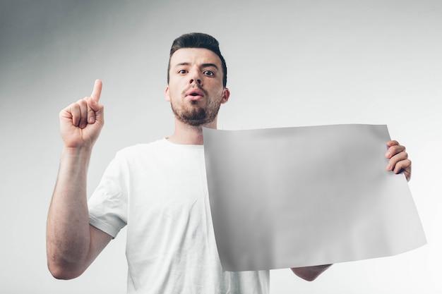 흰색 배경에 고립 남자는 포스터를 보유하고