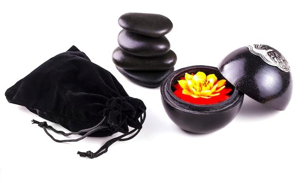 白い香りのキャンドル、花、黒い石とバッグスタイルのタイで隔離されます。