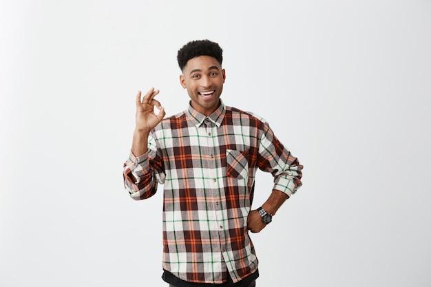 白い壁に分離されました。ポジティブな感情。手でokサインを示す市松模様のシャツでアフロの髪型を持つ若い浅黒い陽気なハンサムな男