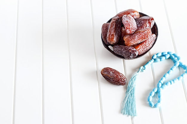 Isolated organic dates medjul and blue rosary in coconut bowl on white background.