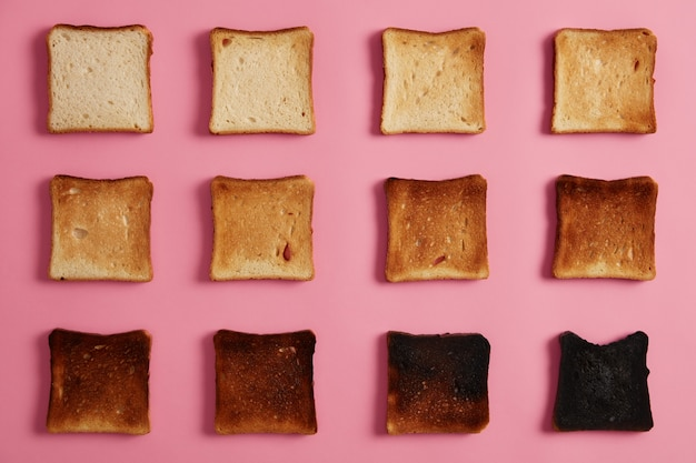 Colpo ambientale isolato di toast di pane in diverse fasi di tostatura su sfondo roseo. l'ultima fetta è completamente bruciata. spuntino per colazione. da non torrefatto a carbonizzato. fotografia di cibo