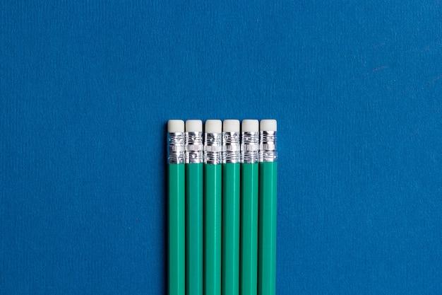 青色の背景に消しゴムで孤立した鉛筆