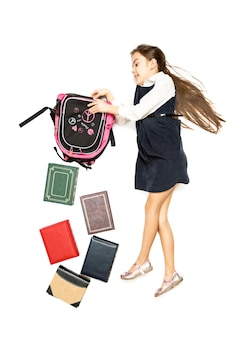 Изолированное фото с высокой точки зрения книг, выпадающих из сумки школьниц