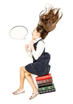 Изолированное фото с высокой точки зрения маленькой девочки, сидящей на книгах и кричащей