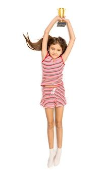 トロフィー カップを頭の上に保持している美しい笑顔の女の子の孤立した写真