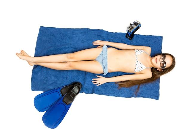 Изолированные фото милая девушка в солнцезащитных очках, лежащая на полотенце и загорающая