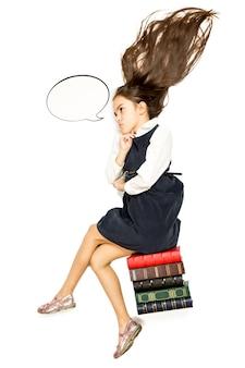 Isolated photo of thoughtful schoolgirl sitting on pile of books
