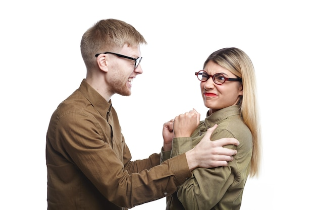Isolated picture of angry fashionable young couple man and woman wearing shirts and eyeglasses having fight. irritated bearded male shaking his girlfriend by her shoulders