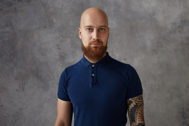 Isolated picture of bald guy with thick red beard and tattoo  while posing against blank  wall  with copy space for your text, information or promotional content