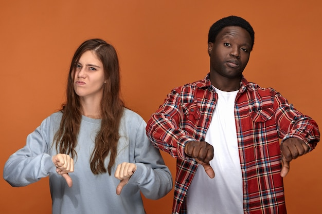 Isolated picture of dissatisfied frowning young european woman and dark skinned man grimacing and making thumbs down gesture, expressing disapproval or dislike, being disappointed with bad movie