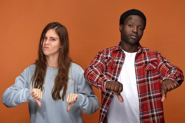 Изолированное изображение недовольной хмурящейся молодой европейской женщины и темнокожего мужчины, гримасничающих и опускающих большие пальцы руки, выражающих неодобрение или неприязнь, разочарованных плохим фильмом