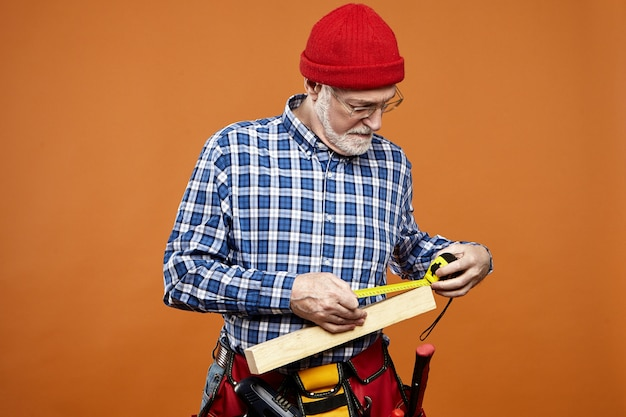 測定テープを使用して木の板の測定を行う、顔の表情に焦点を当てた眼鏡と帽子の深刻なひげを生やしたシニア男性コンストラクターの孤立した写真。手作業と労働