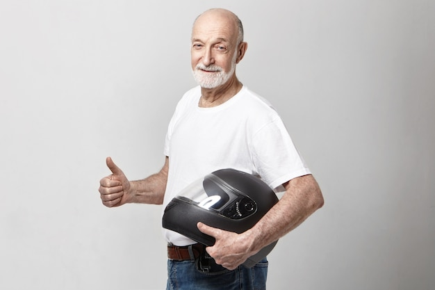 Isolated picture of white senior unshaven european male in casual t-shirt holding motorcycle helmet