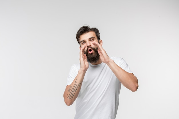 Isolated on pink young casual man shouting at studio
