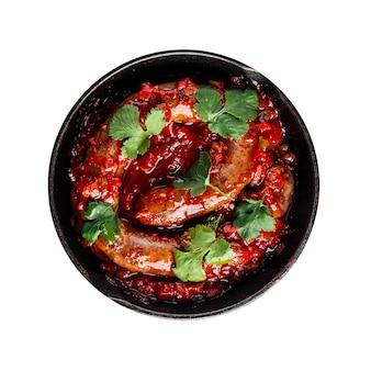 Изолированная тарелка вареной колбасы с томатным соусом