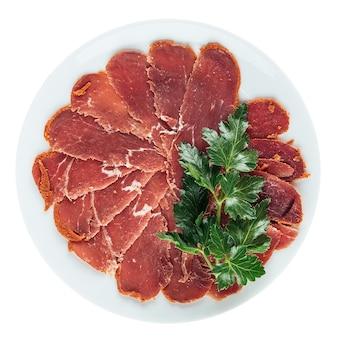 Изолированная тарелка бастурмы из вяленой говяжьей вырезки