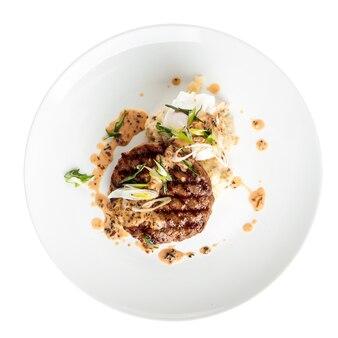 Изолированная тарелка жареной котлеты из говядины с соусом