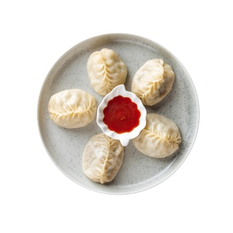 Изолированная тарелка пельменей с мантами с красным соусом