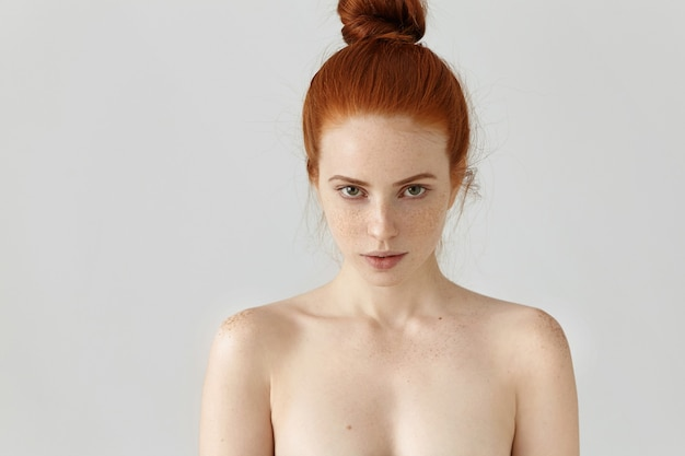 Isolated portrait of attractive young caucasian female with ginger hair knot posing topless indoors