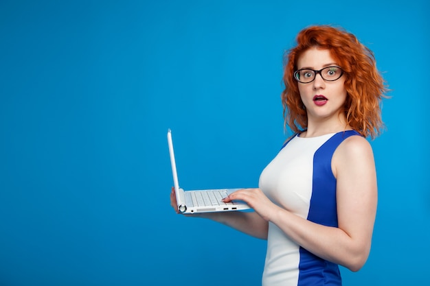 Isolated portrait of a business girl holding a laptop. the girl looks surprised and confused. business and emotional