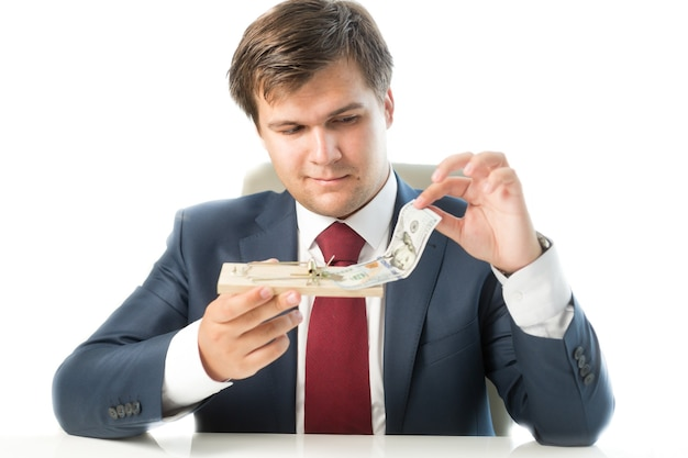 Isolated portrait of businessman holding mousetrap and putting money in it