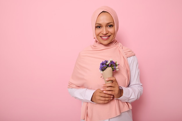 Isolated portrait on colored background of a beautiful muslim arab woman in pink hijab, holding a bouquet of wildflowers in purple shades, wrapped in craft paper, smiles at camera with a toothy smile