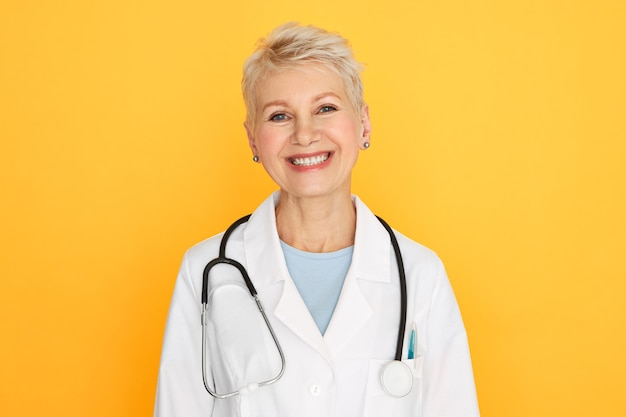 Isolated portrait of confident experienced middle aged female doctor with short blonde haircut looking with happy smile