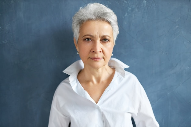 Isolated portrait of confident serious mature female employee with short gray hair frowning posing on blank wall