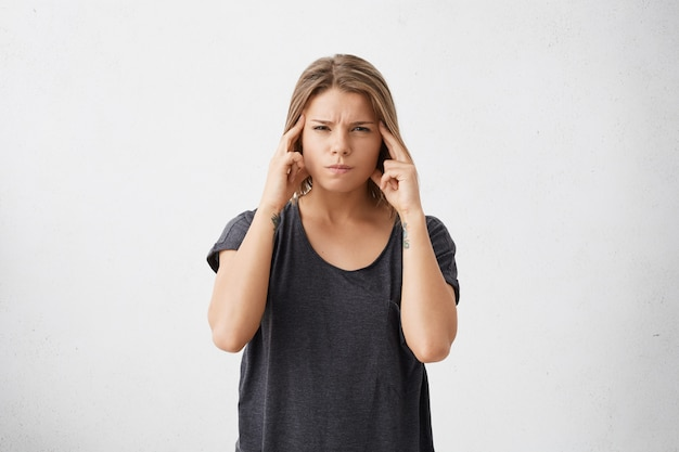Isolated portrait of frustrated stressed out young mixed race female dressed in dark casual t-shirt holding fingers on her temples as if trying to remember something very important.