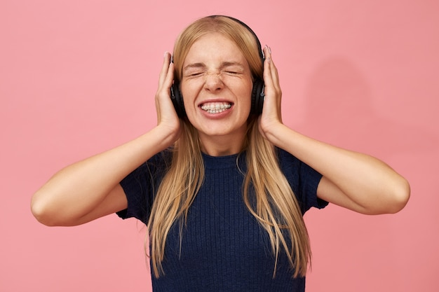 Isolato ritratto di divertenti emotive giovani donne europee con parentesi graffe denti che indossano cuffie wirless chiudendo gli occhi, tenendosi per mano sulle orecchie