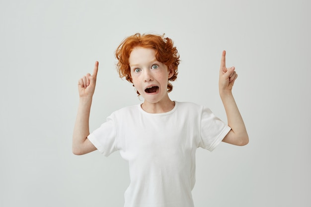 Isolated portrait of funny ginger boy with freckles having surprised look with open mouth, pointing a side with both hands.