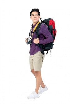 Isolated portrait of handsome young asian tourist man with backpack and camera
