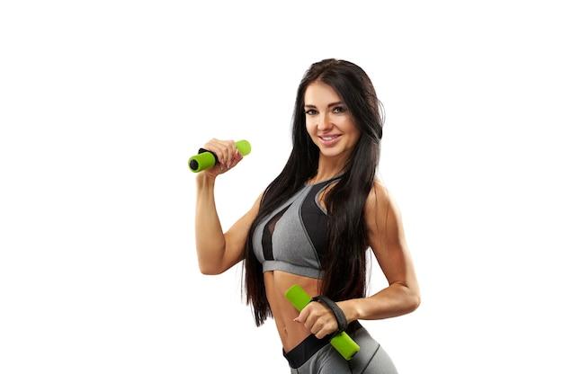 Изолированный портрет спортивной молодой женщины фитнеса с гантелями на белой предпосылке. разрабатывать. спорт. фитнес