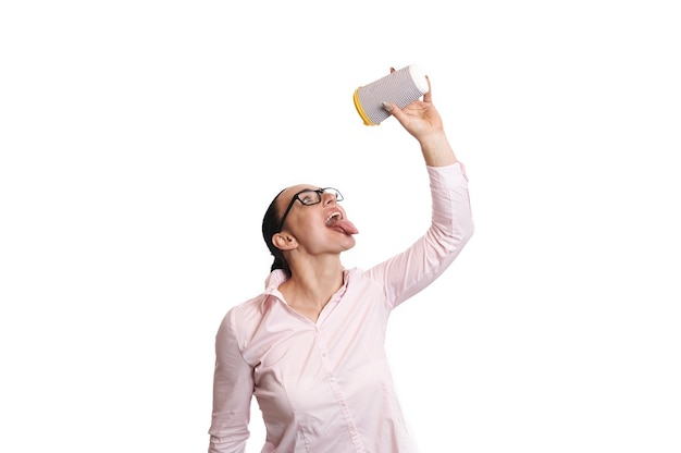 그녀 위에 종이 컵을 들고 내용의 마지막 방울의 절반을 삼키는 것처럼 열린 입으로 포즈를 취하는 젊은 여자의 고립 된 초상화.