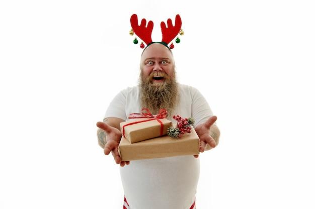 문신 된 팔 머리에 뿔과 후프를 착용 하 고 크리스마스 선물을 제시 과체중 웃음 남자의 고립 된 초상화.
