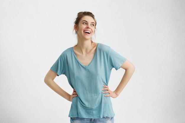 大きな笑みを浮かべて特大の青いトップを着て魅力的な陽気な若いヨーロッパ女性の孤立した肖像画は広く笑みを浮かべて、屋内で楽しんでいる間、幸せで屈託のない気持ちで、喜びと喜びをよそ見