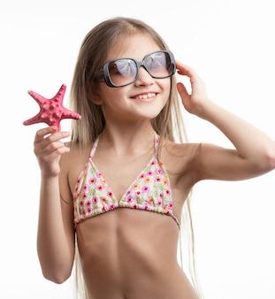 Изолированный портрет милой улыбающейся девушки в солнцезащитных очках, позирующей с морской звездой