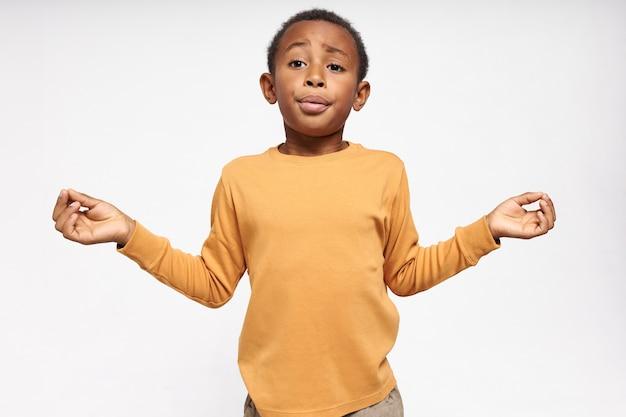 Изолированный портрет эмоционального смешного темнокожего маленького мальчика, взявшегося за руки в жесте мудры, выдыхая, делая дыхательные упражнения, чтобы успокоиться